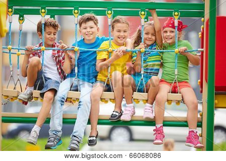 Cheerful kids sitting on swing and looking at camera