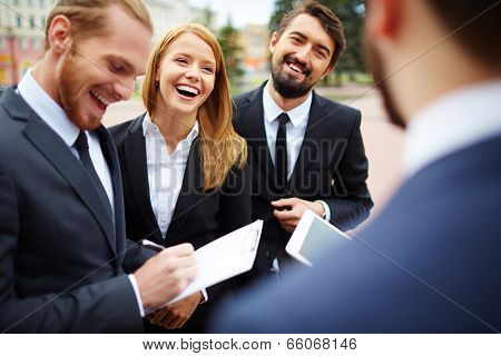 Happy businesswoman looking at colleague while discussing ideas at meeting outside