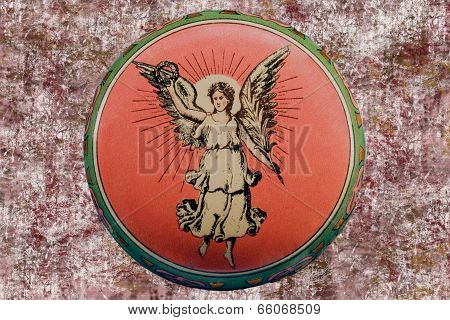 Old Tin Box About 1910 With Angel On Grunge Background