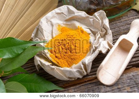 Tumeric powder spice on wooden board