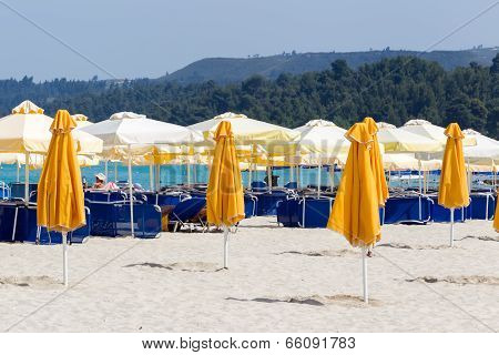 Closed Parasols On The Beach With Sunchairs And Umbrellas In The Background.