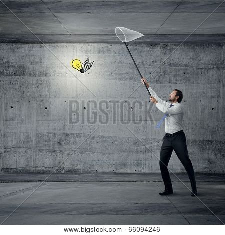 Young businessman with butterfly net in his hands