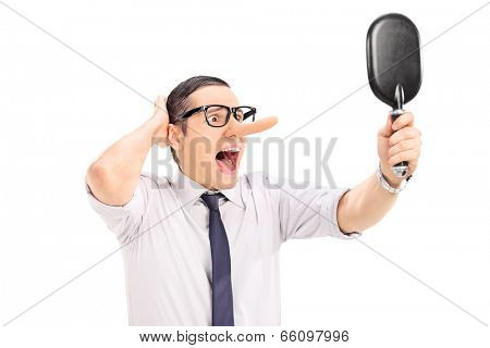 Furious man with long nose looking in a mirror isolated on white background