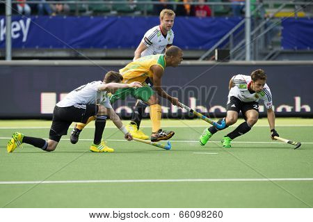 THE HAGUE, NETHERLANDS - JUNE 1: South African Hockey Player Julian HykesIs being stopped by two German defenders during the World Cup Hockey. GER-RSA 4-0