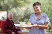 pic of meals wheels  - smiling home carer serving meal to elderly man - JPG