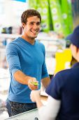 stock photo of cashiers  - happy young man handing over credit card to a female cashier at till point - JPG