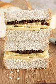 stock photo of home-made bread  - Rustic style hand cut Cheddar cheese and pickle sandwich made with home made bread - JPG