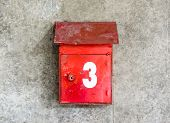 stock photo of postbox  - old single vintage red postbox number three on grunge concrete wall - JPG
