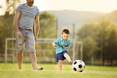 image of football pitch  - Young father with his little son playing football on football pitch - JPG