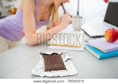 Closeup On Chocolate And Young Woman Studying In Background