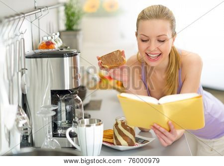 Young Woman Eating Toast With Chocolate Cream And Reading Book