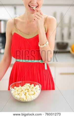 Closeup On Young Woman Eating Popcorn In Kitchen