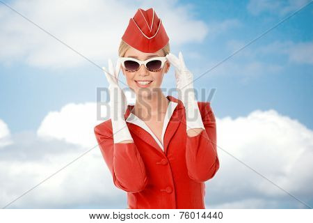 Charming Stewardess Dressed In Red Uniform And Vintage Sunglasses. Sky With Clouds Background.