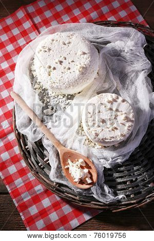 Cottage cheese on gauze on wicker mat on fabric background