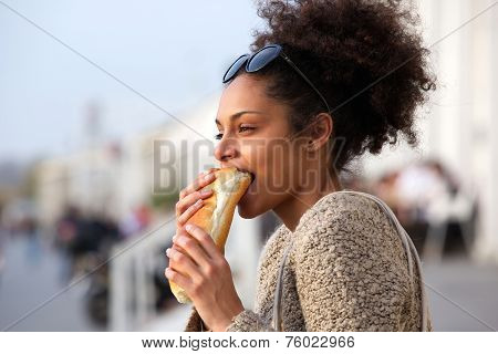 Beautiful Young Woman Eating Sandwich Outdoors