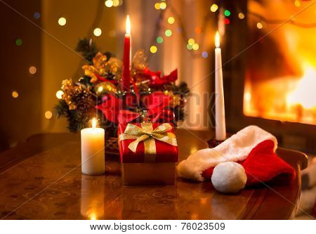 Christmas Photo Of Burning Candles With Giftbox Against Fireplace