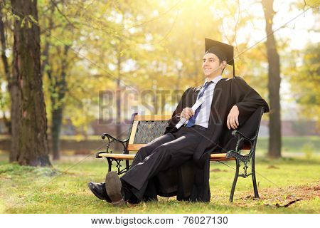 College graduate enjoying in park seated on a bench