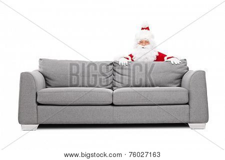 Santa Claus hiding behind a sofa isolated on white background