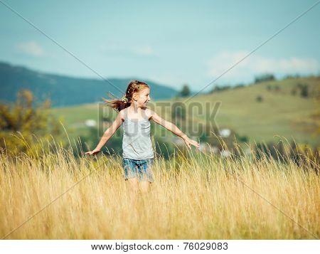 cute little girl runs through a beautiful meadow in the mountains.