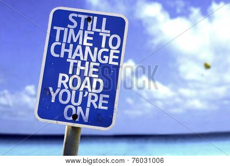 Still Time To Change the Road You're On sign with a beach on background