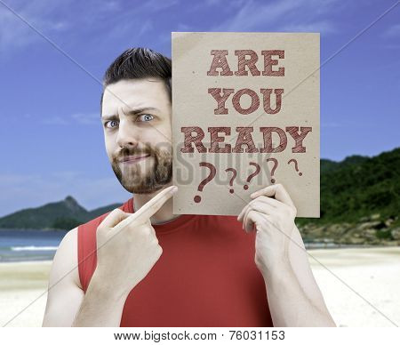 Man holding a card with the text Are you Ready? on a beach background