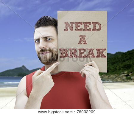 Man holding a card with the text Need a Break on a beach background