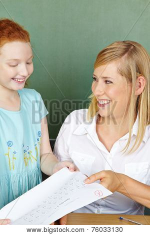 Teacher giving girl test back with a very good grade in elementary school