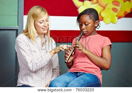 Teacher helping student to play flute in music school