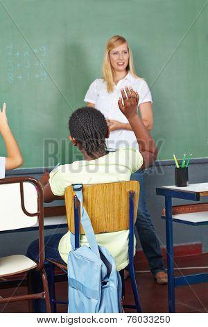 Children raising hands in elementary school math class