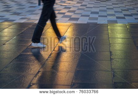 Young Man Walking On Wet Pavement