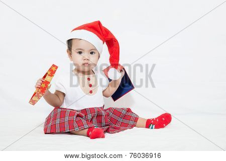 Photo Of Curious And Surprised Asian Baby In Santa Cap Looking At Giftbox