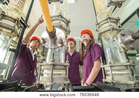 Group Of Engineer Students University Looking In Machine In Laboratory
