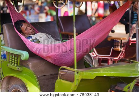 SIEM REAP, CAMBODIA, DECEMBER 3, 2012: A tuk-tuk driver is taking a nap lying in a hammock inside the car in Siem Reap, Cambodia