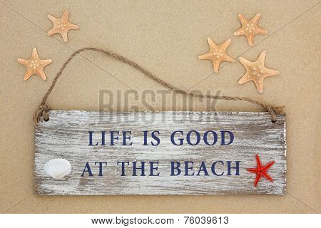 Life is good at the beach sign with starfish and cockle shell on sand background.