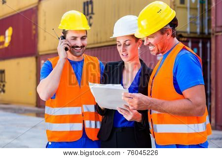 Worker and manager of shipment company discussing freight or shipment documents, one man is using phone or walkie-talkie