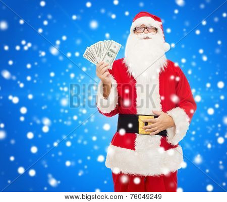 christmas, holidays, winning, currency and people concept - man in costume of santa claus with dollar money over blue snowy background