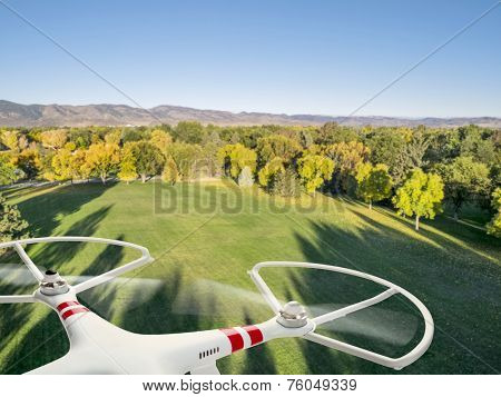 drone flying over a park in fall colors under morning light with deep long shadows