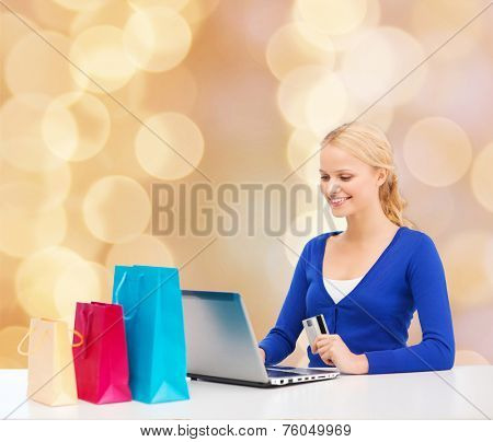 christmas, holidays, technology and shopping concept - smiling woman with shopping bags, credit card and laptop computer over beige lights background