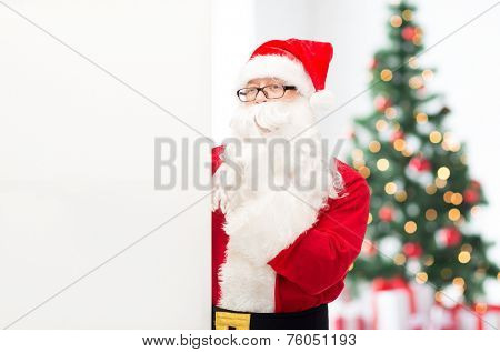 christmas, holidays, advertisement and people concept - man in costume of santa claus with white blank billboard making hush gesture over living room with tree