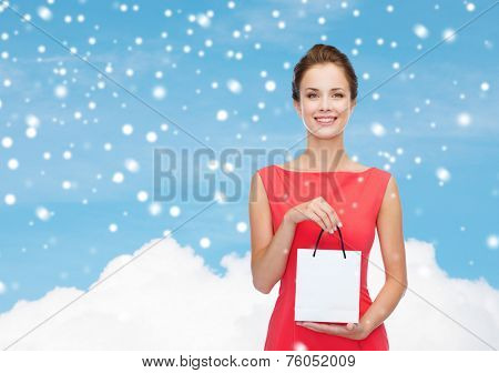 shopping, sale, christmas and holiday concept - smiling elegant woman in red dress with small shopping bag over blue sky with cloud and snow background
