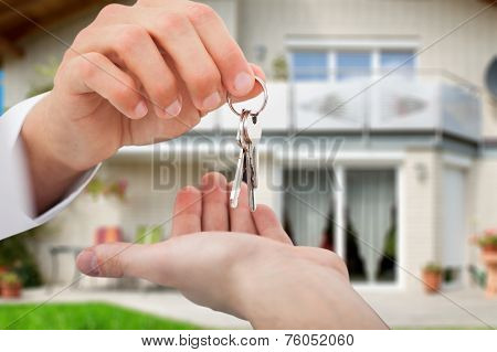 Real Estate Agent Giving Keys To Owner Against New House