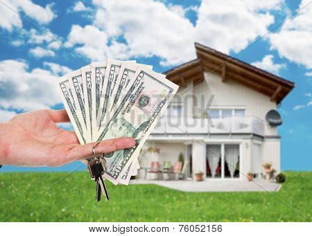 Hand Holding Key And Dollar Notes Against House