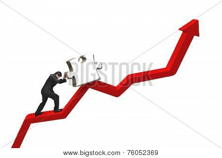 Businessman Pushing Heavy Jigsaw Puzzle Upward On Red Trend Line
