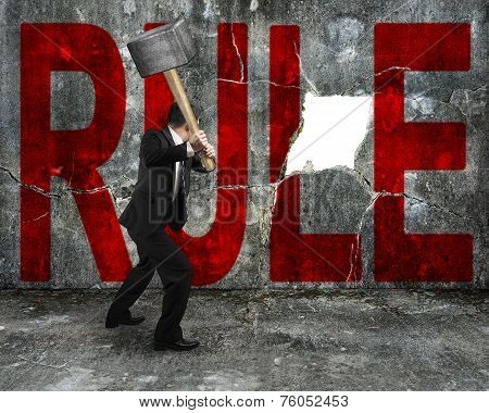 Businessman Holding Sledgehammer Hitting Red Rule Word On Concrete Wall