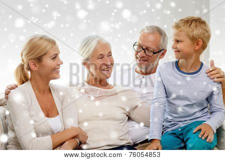 family, adoption, generation and people concept - happy family sitting on couch at home