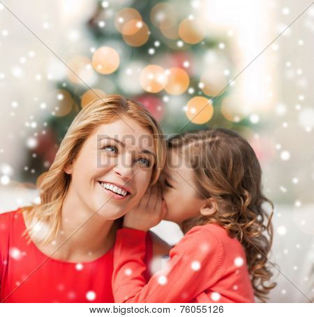 people, motherhood, family, christmas and adoption concept - happy mother and daughter whispering something into ear at home