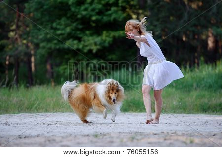 Beautiful young girl in a white dress and her collie dog