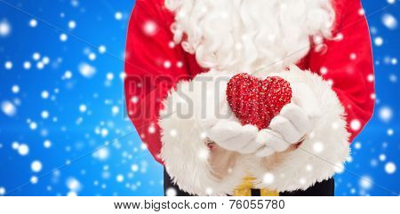christmas, holidays, love, charity and people concept - close up of santa claus with heart shape decoration over blue snowy background