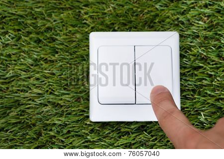 Man's Finger Pointing At Switch On Grass