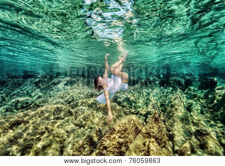 Active woman with pleasure swimming underwater, enjoying beautiful coral garden, relaxation in the sea, summer vacation concept